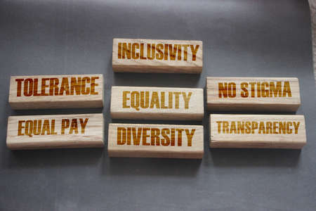 Inclusivity tolerance transparency equality diversity words on wooden blocks. Accepting others individuality concept, top view gray background