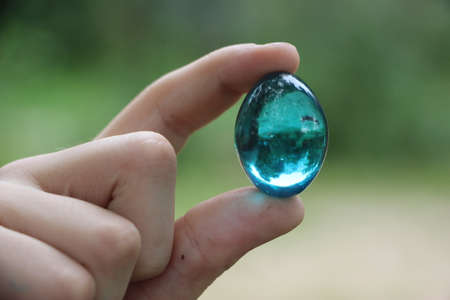 Crystal glass ball in human hand on defocused grass background. Saving environment, save clean green planet, ecology concept.