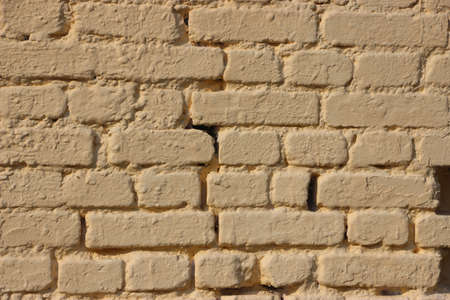 old gringe vintage weathered brick wall texture painted into solid pale yellow. Banque d'images