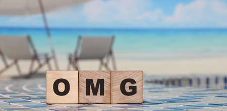 The word OMG from wooden cubes. Relaxed beach background. Lifestyle concept
