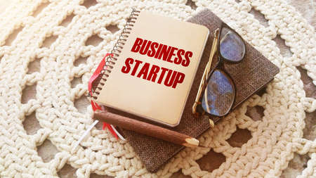 Business startup written on a notebook with pen, glasses on crochet cloth. Successful new business case concept