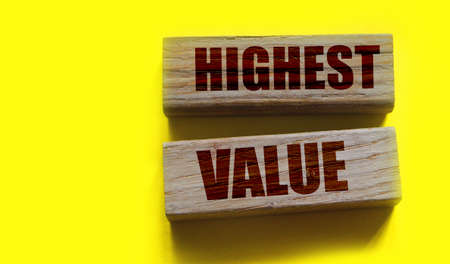 Highest values words on wooden building blocks isolated on yellow. Social, business and education concept.