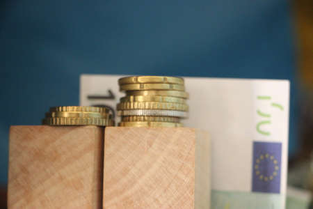 Two Stacks of Euro coins and 100 Euro bill on the background. Growing business profit concept.