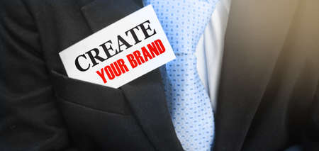 Create Your Brand words on card in Businessman upper suit pocket. Business startup branding marketing concept