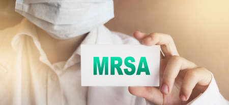 Doctor, wearing face protective mask shows a card with the text MRSA. Medical concept.
