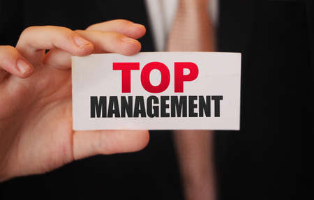 Businessman shows a card with word Top Management. CEO position business concept.