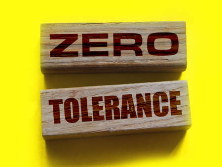 Zero tolerance - words from wooden blocks with letters, severely punishing all unacceptable behavior, zero tolerance concept, yellow background.