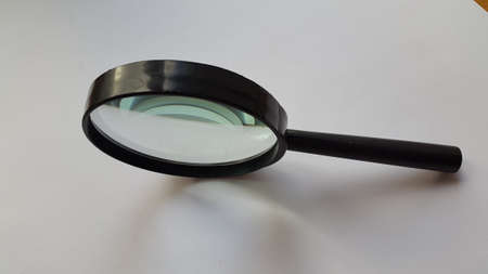 Magnifying glass placed over white sheet of paper with nice mild shadow.