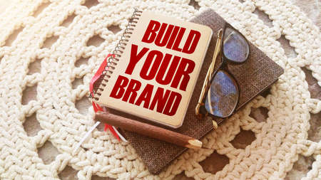 Build Your Brand words on a cover of spiral copybook. Pen, glasses notebook. Branding rebranding marketing business concept.