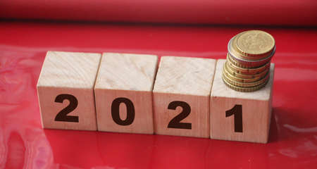 Year 2021 on wooden cubes and stack of coins. economy growth and recovery, increase money saving and investment concept. Zdjęcie Seryjne