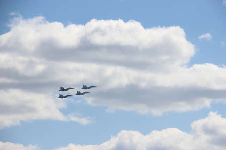 4 military Spitfire fighters silhouettes in blue sky with white clouds. Military concept 版權商用圖片