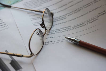 Business legal document concept: Pen and glasses on a agreement form.