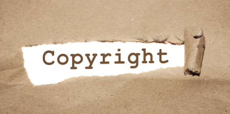 Copyright word uner torn paper. Legal marking of the brand, business concept.