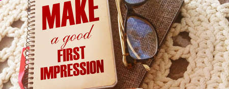 Make a Good First Impression written on book cover, eyeglasses and pen. Business career motyvation concept.