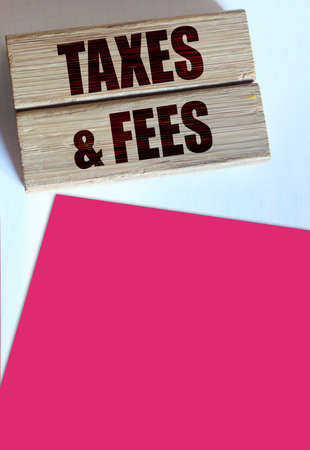 Taxes and fees Text on the wooden blocks, magenta pink paper. Business concept.