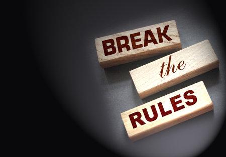 Break the rules phrase on wooden blocks on dark gray. Behavior concept or innovative business management concept