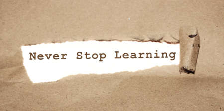 Brown torn Paper and yellow background with never stop learning written. Education concept