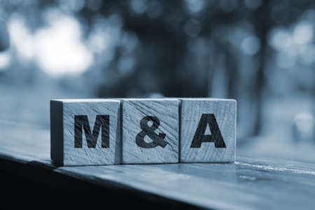Wooden cubes with the abbreviation M and A on them. Business merges and aquisitions concept.