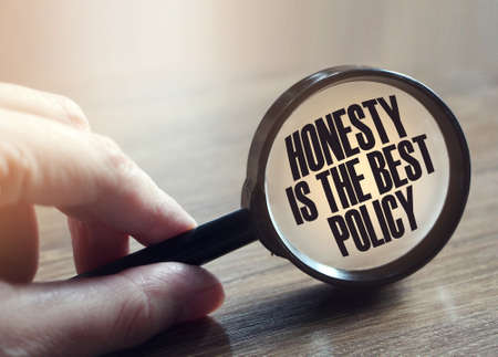 Honesty Is The Best Policy Messageunder magnifying glass in hand. Marketing business concept. Standard-Bild