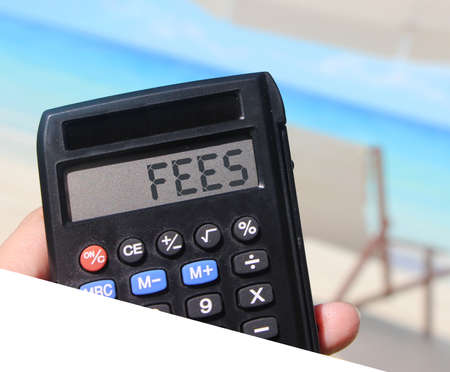 Calculator with the word FEES on the display with relaxed blurred beach landscape background. Selective focus. Taxes and fees business concept