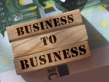 Business to business on Wooden blocks put on 100 euro bills. B2B marketing concept Archivio Fotografico