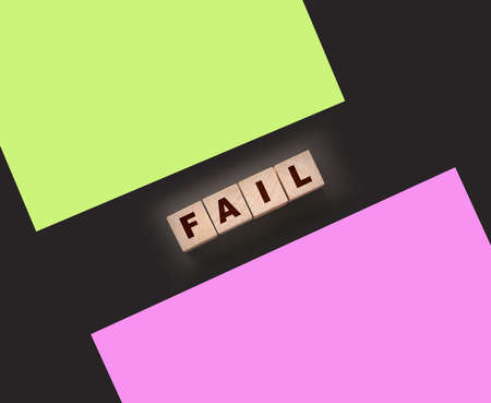 FAIL Word text Written In Wooden Cube blocks on black background. Business crisis concept.