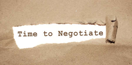 The text Time to negotiate appearing behind torn paper. Business concept Archivio Fotografico