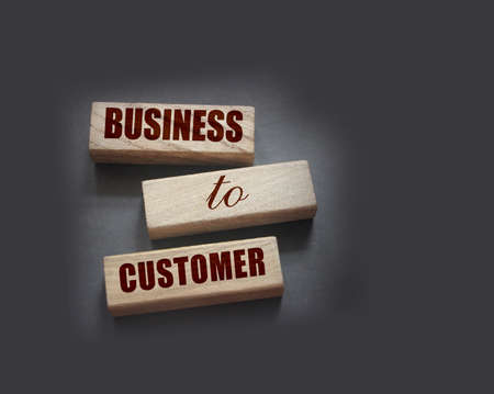 Business to Customer inscription made on wooden blocks on grey tabletop. B2C business marketing concept