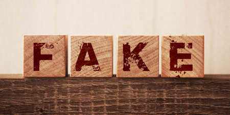 Fake word letters on wooden blocks, over dark oak table. True and lies in businiess and news concept Archivio Fotografico