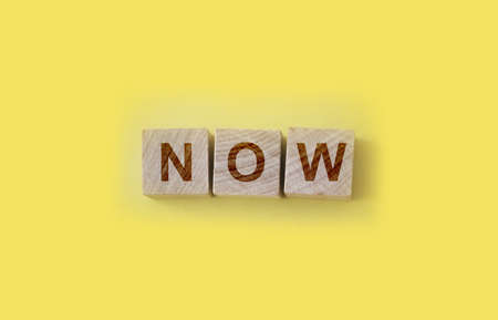 Now text word cube on yellow background Archivio Fotografico