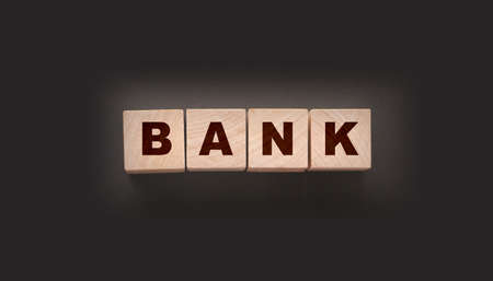 Bank word on wooden cubes on black . Banking saving financial investment concept