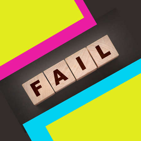 FAIL Word text Written In Wooden Cube blocks on black background. Business crisis concept