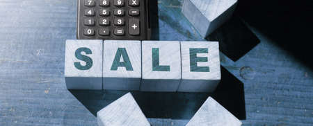 Word SALE on wooden cubes and calculator on wooden table. Business concept Archivio Fotografico