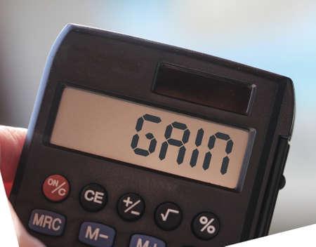 Gain text on calculator display, defocused sea. business concept Archivio Fotografico