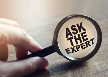 Magnifying glass with words ask an expert on wooden table. Business concept