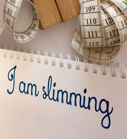 Measuring tape and copybook with I am slimming text. Weight loss or diet healthy lifestyle concept