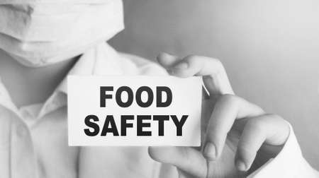 Doctor holding a card with text Food Safety, medical concept Archivio Fotografico