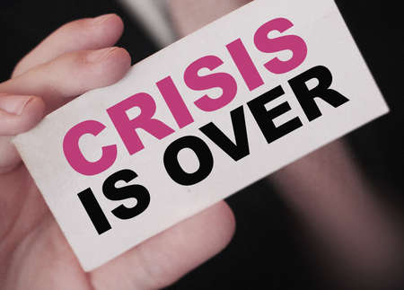 Crisis is over words on card Businessman is holding. Word Crisis, risk managent in business concept