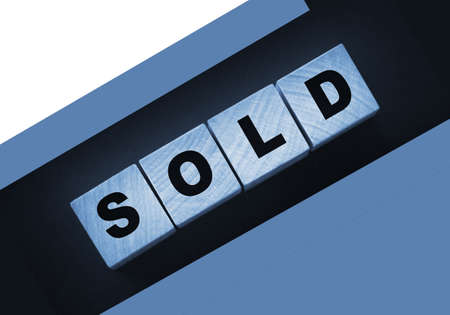 Sold Word Written In Wooden Cubes on black background. Real estate business concept