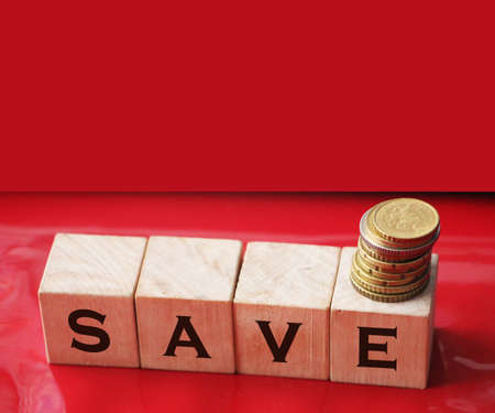 Word Save on wooden cubes with coins. Money saving and taxes saving business concept.