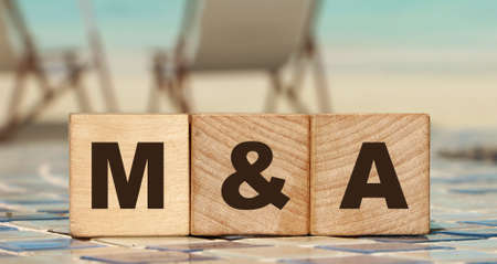 M and A or Merger and Acquisition text written on a wooden cubes. Business concept.