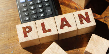 Wooden cubes with the word PLAN and calculator on wooden table. Business plan concept. Covid-19 crisis. Copy space for advertisers.