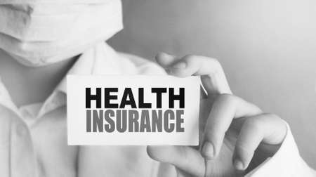 Health insurance words on the card in hands of Medical Doctor. Healthcare concept. Archivio Fotografico