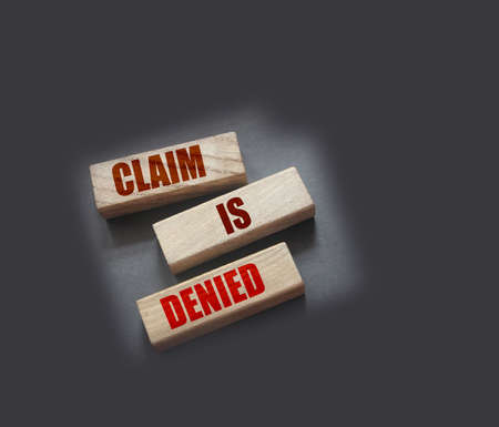 Claim is denied on Wooden Blocks on dark gray background with copyspace. The answer is No. Business financing sponsorship concept.