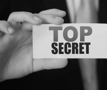 Businessman hand holding card with words Top Secrets. Business concept. Archivio Fotografico