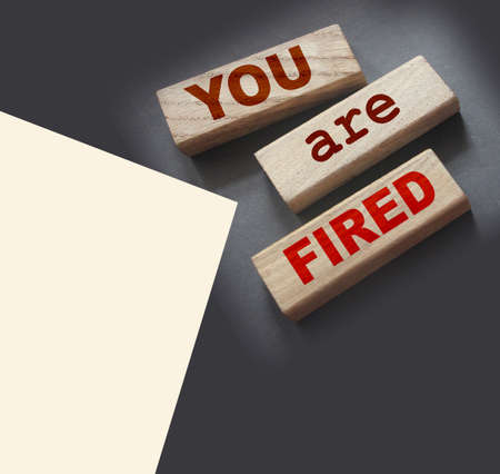 You are fired written on a wooden blocks with copyspace. Crisis labor force cut business concept. Archivio Fotografico