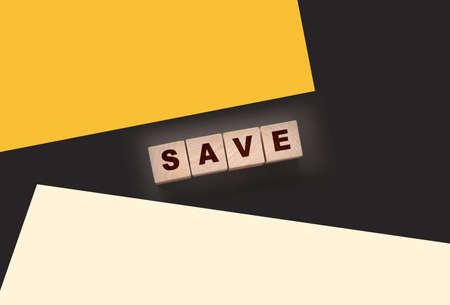 Text SAVE on a wooden cube blocks on black background. Money saving concept.