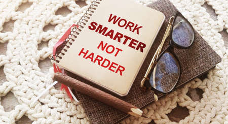 Pen ,, glasses and spiral notebook with Work Smarter Not Harder words on crochet cloth background. Career and business concept