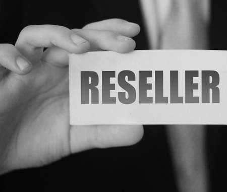 Businessman holding a card with Reseller word. Reselling business concept.