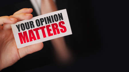 Businessman shows a card with text Your Opinion Matters. Business teambuilding concept.